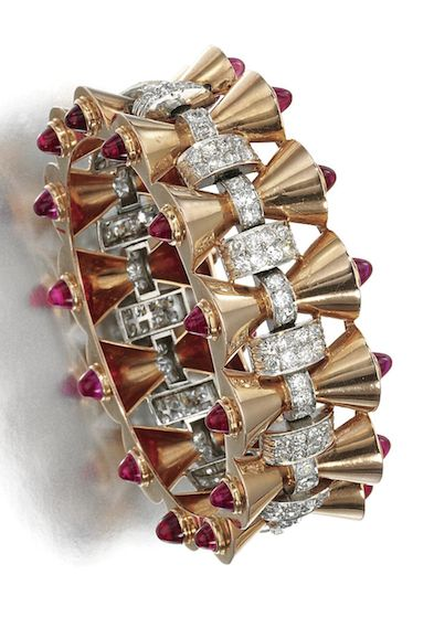 SYNTHETIC RUBY AND DIAMOND BANGLE, 1940S The hinged bangle designed as a series ...