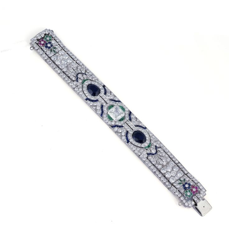 GATTLE. An Art Deco emerald, sapphire and diamond bracelet.Designed as a…...