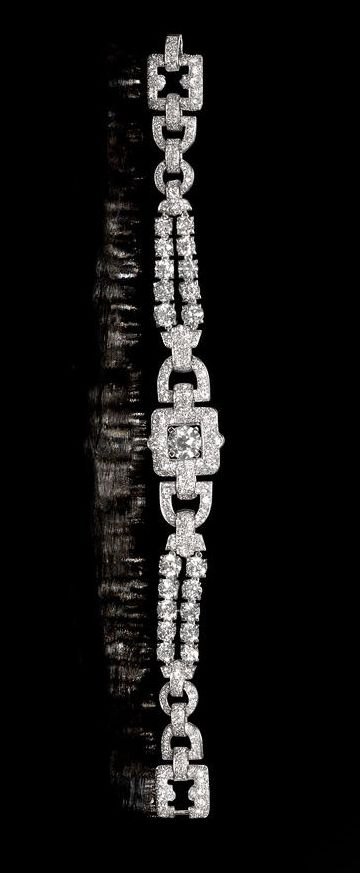 A diamond bracelet, by Cartier, circa 1935 Designed as a series of buckle-shaped...