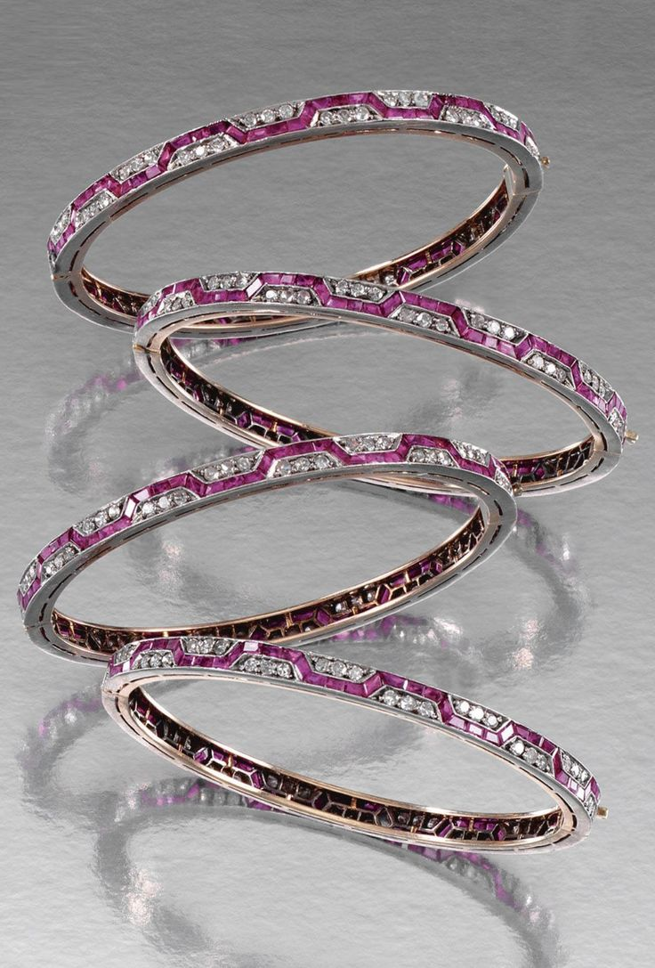 FOUR EARLY ART DECO RUBY AND DIAMOND BANGLES, CIRCA 1910. Each hinged bangle of ...