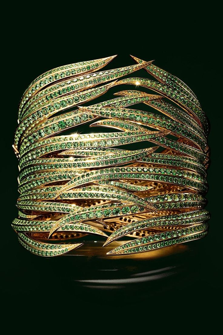 Tsavorites and yellow sapphire leaves wrap the wrist in this 18k gold cuff.