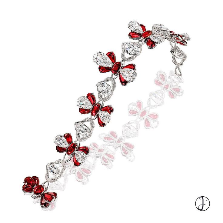 Oval and pear-shaped rubies are combined to create a butterfly-in-flight effect....