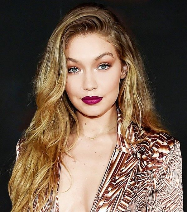 Gigi Hadid deep side part and bold berry lips make for a bombshell beauty look. ...