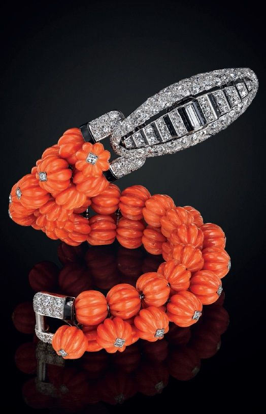 CARTIER An art deco carved coral, onyx, diamond, and platinum bracelet, by Carti...