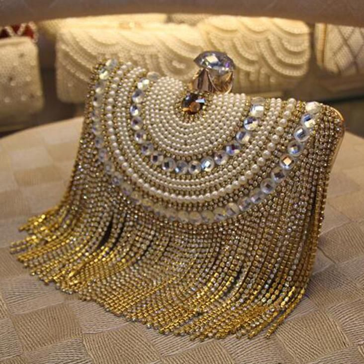 Opulent gold chain tassel clutch with diamonds and pearls decorating the front. ...