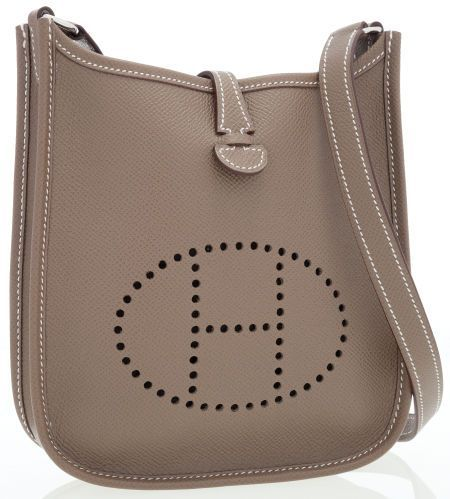 The exterior of this beloved Hermes Evelyne miniature crossbody bag is done in E...